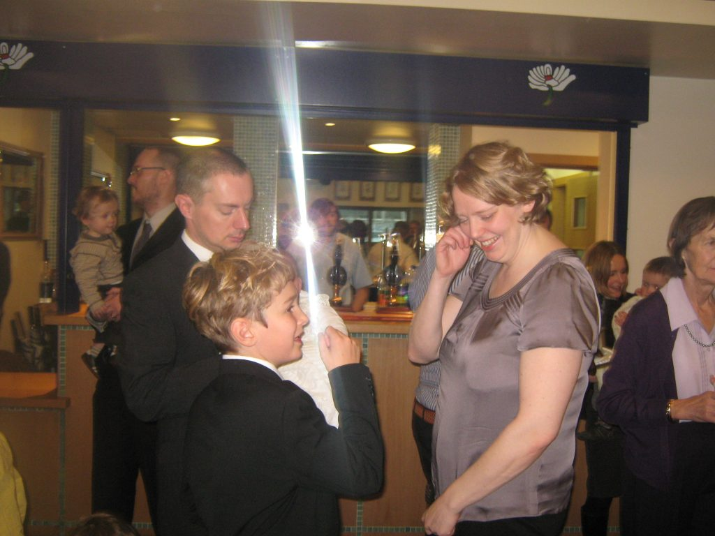 "At Tolamo's christening at Headingley cricket & rugby club, Leeds October 2010. Catherine and Lesejo the proud parents; us all admiring the Yorkshire outpost of the rainbow nation. Tolly was such a beautiful colour when he was born, Peggy said she wanted to ""...lick him?!"" I suggested excitedly. ""Kiss him. All over."" She said, much more demurely."